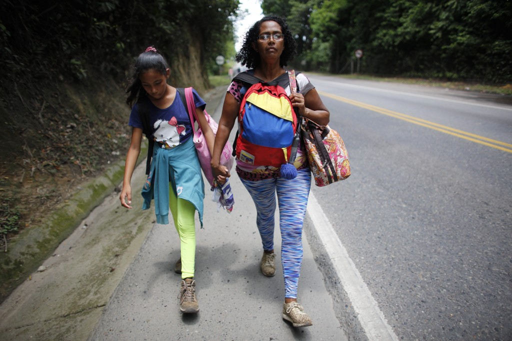 In this Sept. 2, 2018 photo, Venezuelan Sandra Cadiz holds the hand of her 10-year-old daughter Angelis as they walk on the shoulder of the road durin
