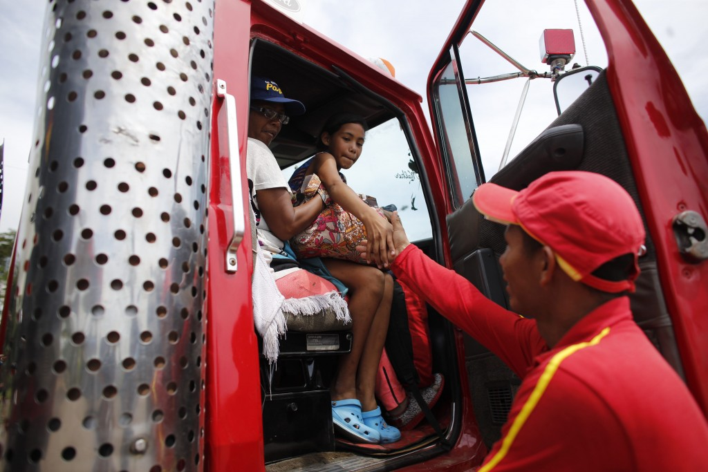 In this Sept. 3, 2018 photo, Venezuelan Sandra Cadiz and her 10-year-old daughter Angelis, thank gas station worker Manuel Velasquez after he helped t...