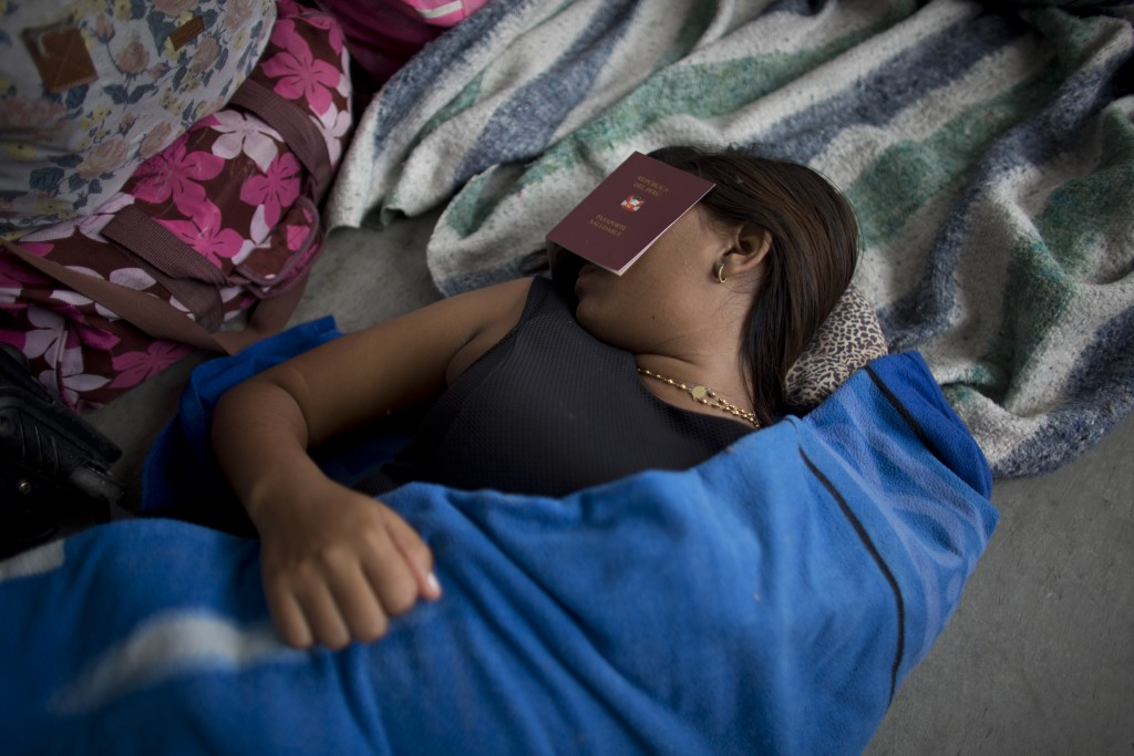 "In this Sept. 7, 2018 photo, a Venezuelan woman covers her eyes with a Peruvian ""health"" passport to get some sleep near the Peruvian immigration offi"