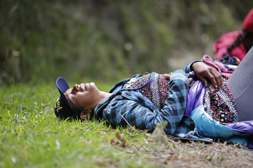 In this Sept 1, 2018 photo, fatigued Venezuelan Sandra Cadiz throws herself on the grass as she takes a break from walking to the Berlin paramo leadin...