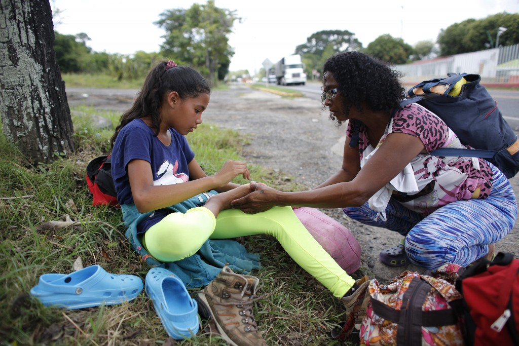 In this Sept. 2, 2018 photo, Venezuelan Sandra Cadiz inspects the foot of her 10-year-old daughter Angelis who complained of pain as they take a break