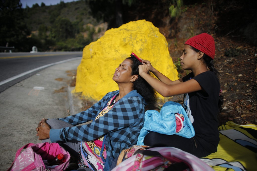 In this Sept. 1, 2018 photo, 10-year-old Venezuelan Angelis combs the hair of her mother Sandra Cadiz as they take a break from walking to the Berlin