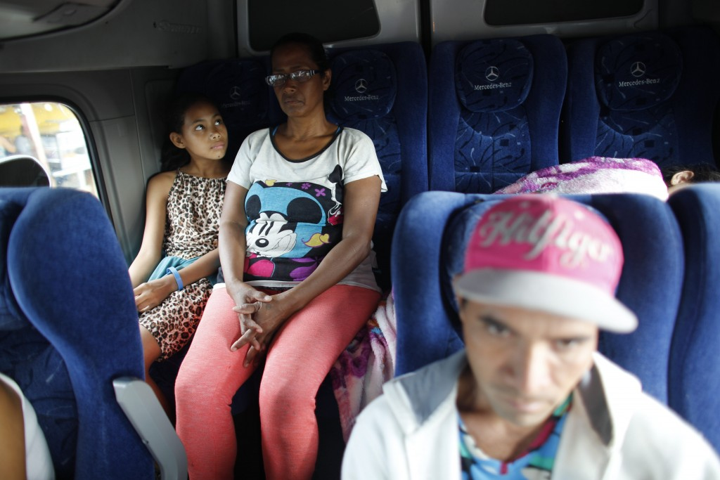 In this Sept. 4, 2018 photo, 10-year-old Venezuelan Angelis looks up at her mother Sandra Cadiz on the back of a bus at the stop in San Juan de la Paz