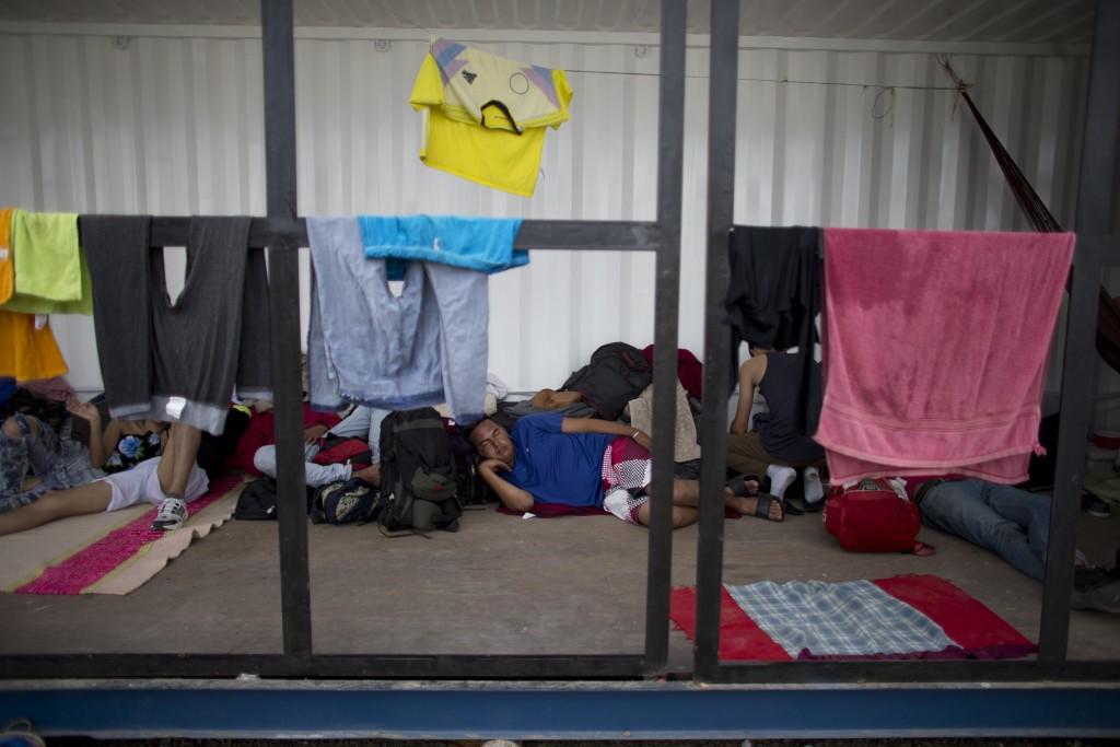 In this Sept. 7, 2018 photo, Venezuelans rest as they wait in a shipping container near Peru's immigration office in Aguas Verdes, Peru. Venezuelan mi...