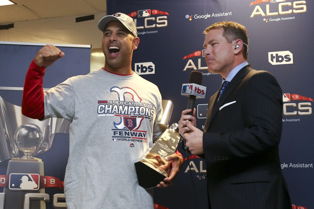 Boston Red Sox manager Alex Cora celebrate with the William Harridge Trophy in the clubhouse after defeating the Houston Astros 4-1 in the baseball Am