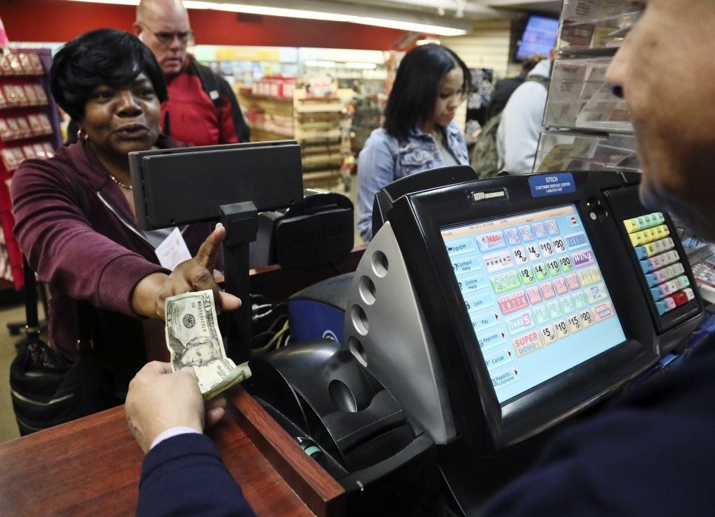 Annette Gray, left, from Valley Stream, N.Y., buys lottery tickets Friday Oct. 19, 2018, in New York. The estimated jackpot for Friday's Mega Millions...