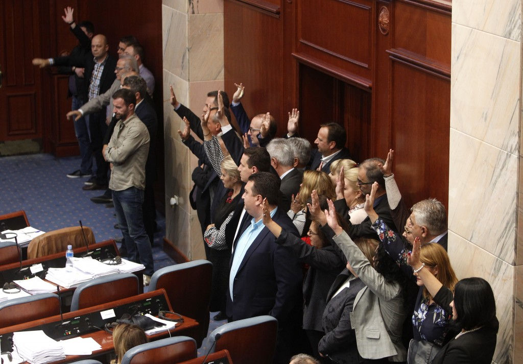 Lawmakers of the opposition VMRO-DPMNE stand on the right and react during the voting on proposal on a motion for constitutional revision during a ses...