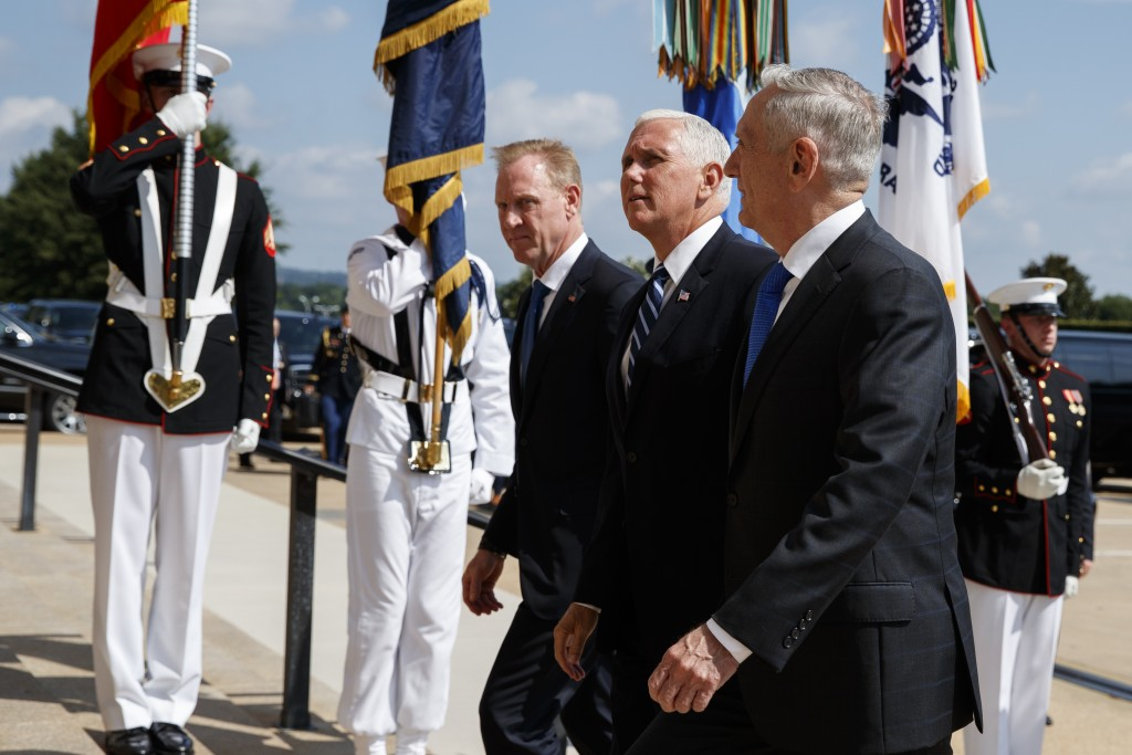FILE - In this Aug. 9, 2018 file photo, Vice President Mike Pence, center, is greeted by Deputy Secretary of Defense Pat Shanahan, left, and Secretary