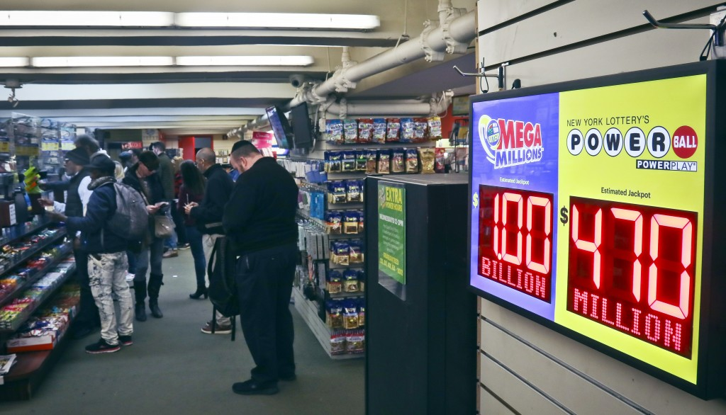 Lottery players buy Mega Millions lottery tickets, Friday Oct. 19, 2018, in New York. The estimated jackpot for Friday's drawing has soared to $1 bill...