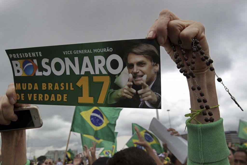 A supporter of presidential candidate Jair Bolsonaro, of the right-wing Social Liberal Party, carries a rosary during a campaign rally in Brasilia, Br...