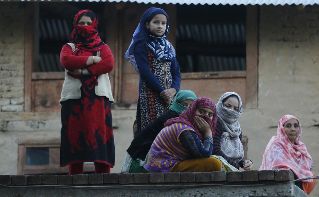 Kashmiri women and girls watch the funeral procession of a civilian Uzair Mushtaq in Kulgam 75 Kilometers south of Srinagar, Indian controlled Kashmir