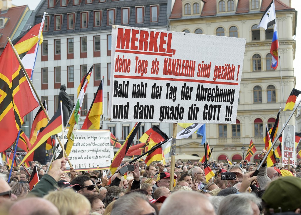 "People carry a sign reading ""Merkel, your days are counted, the day of payoff is near, may God have mercy with you"" during a rally of PEGIDA (Patrioti"