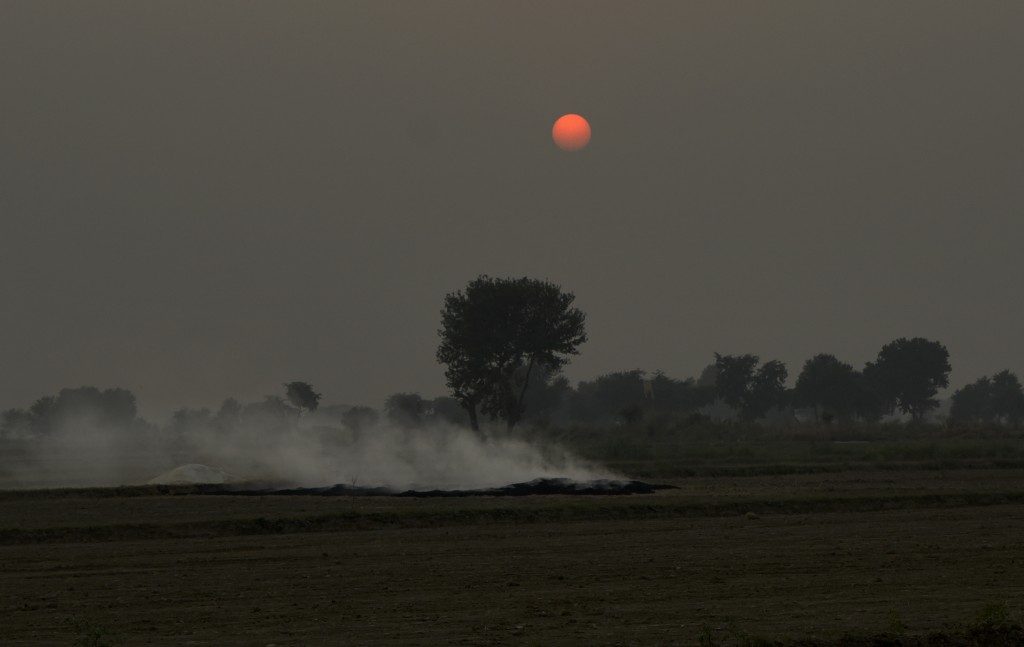 Smoke rises as farmers burn crop stubble during sunset at a village near Mathura, India, Saturday, Oct. 20, 2018. The Indian capital and large parts o