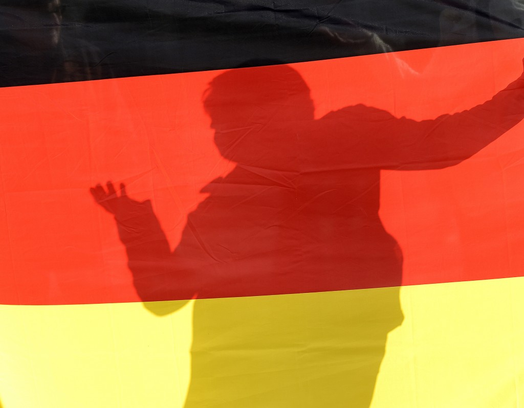 A person is seen through a German national flag during a rally of PEGIDA (Patriotic Europeans against the Islamization of the West) in Dresden, German...