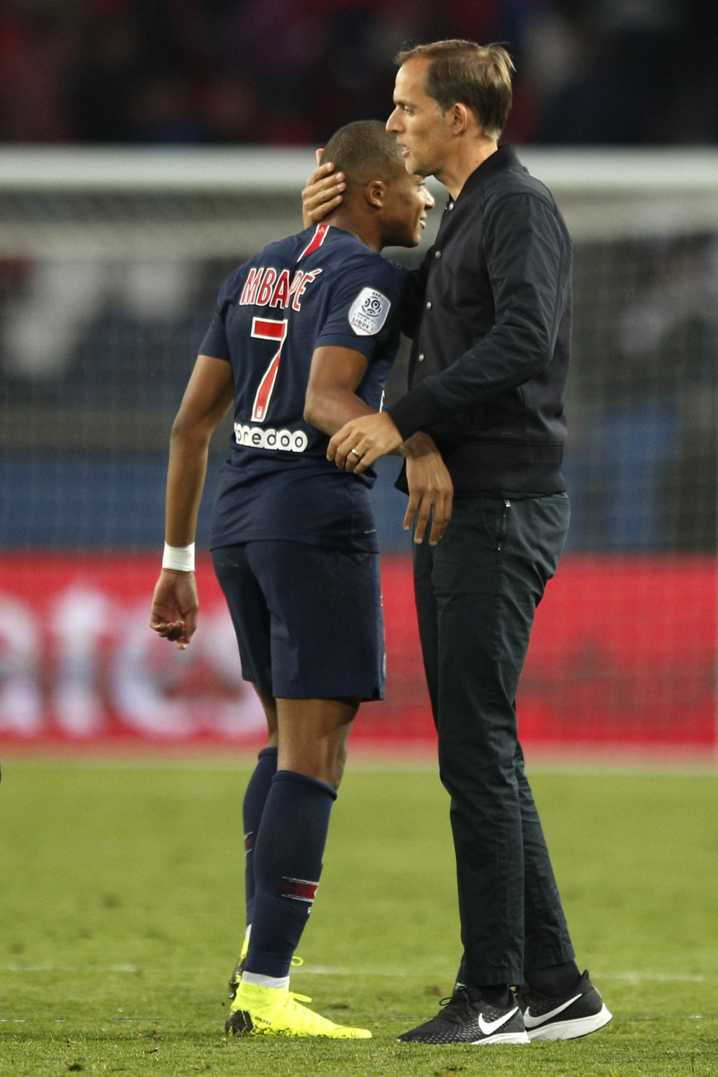 PSG coach Thomas Tuchel, right, embraces PSG's Kylian Mbappe after the French League One soccer match between Paris-Saint-Germain and Amiens at the Pa...