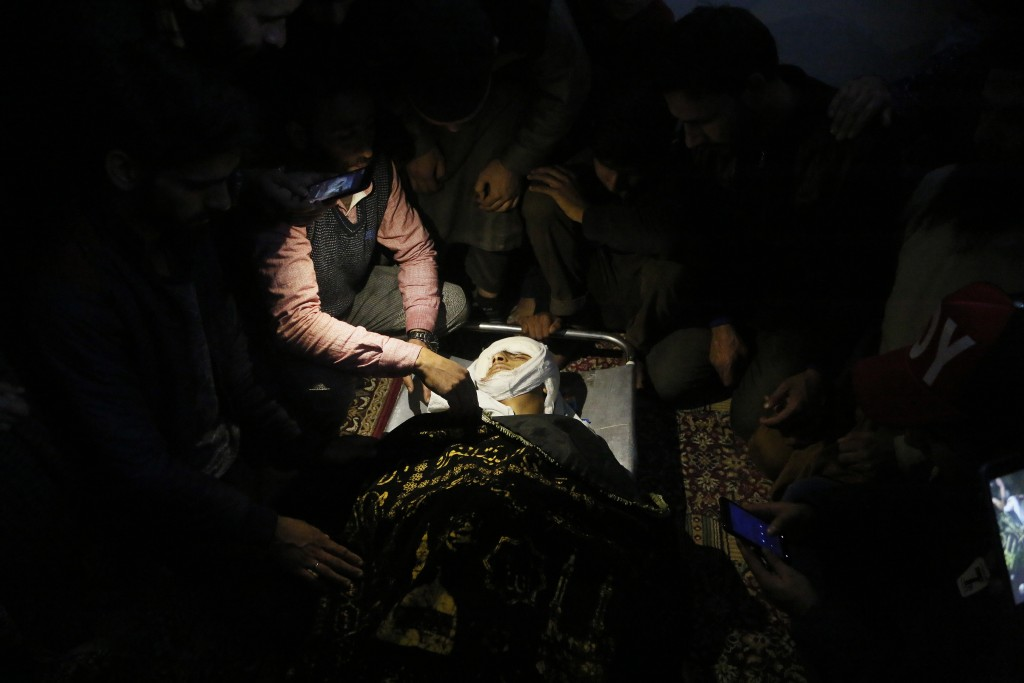 Kashmiri villagers sit next to the body of Uzair Mushtaq inside a mosque before his funeral in Kulgam 75 Kilometers south of Srinagar, Indian controll