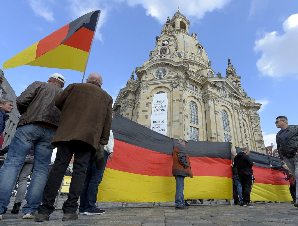 People with German national flags wait for the beginning of a rally of PEGIDA (Patriotic Europeans against the Islamization of the West) in Dresden, G...