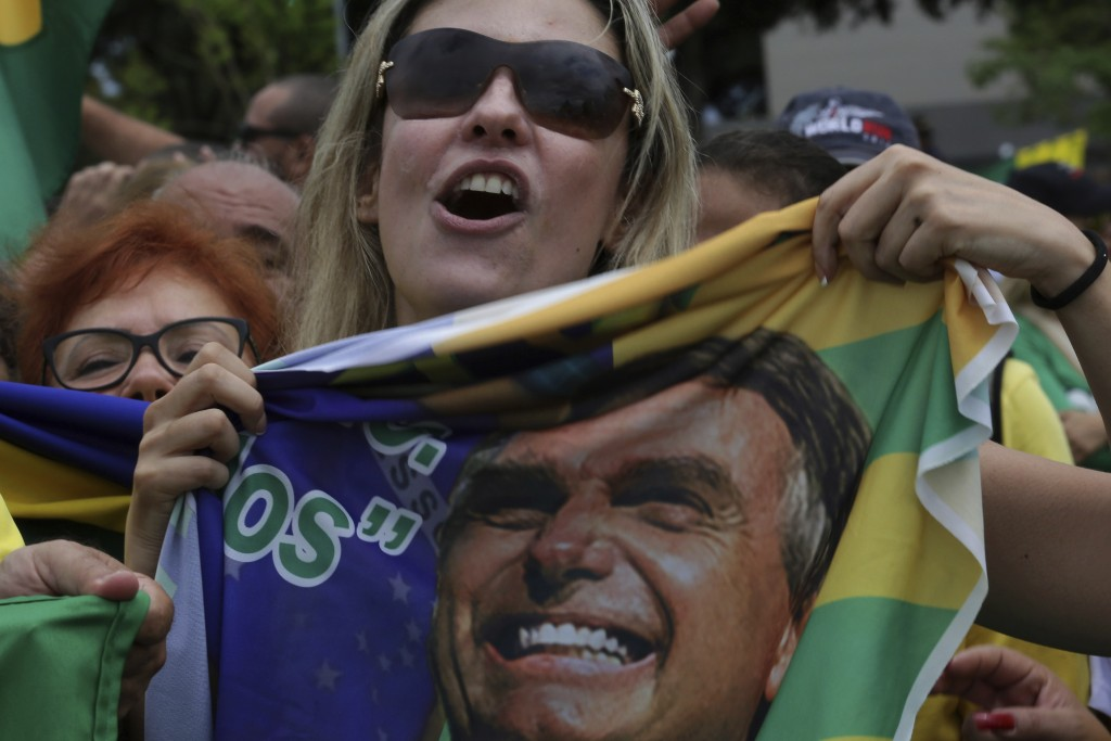 Supporters of presidential candidate Jair Bolsonaro, of the right-wing Social Liberal Party, rally in Brasilia, Brazil, Sunday, Oct. 21, 2018, one wee...