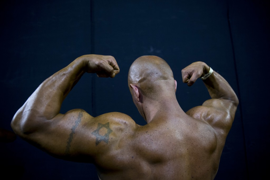 In this Thursday, Oct. 18, 2018 photo, a contestant exercises backstage during the National Amateur Body Builders' Association competition in Tel Aviv