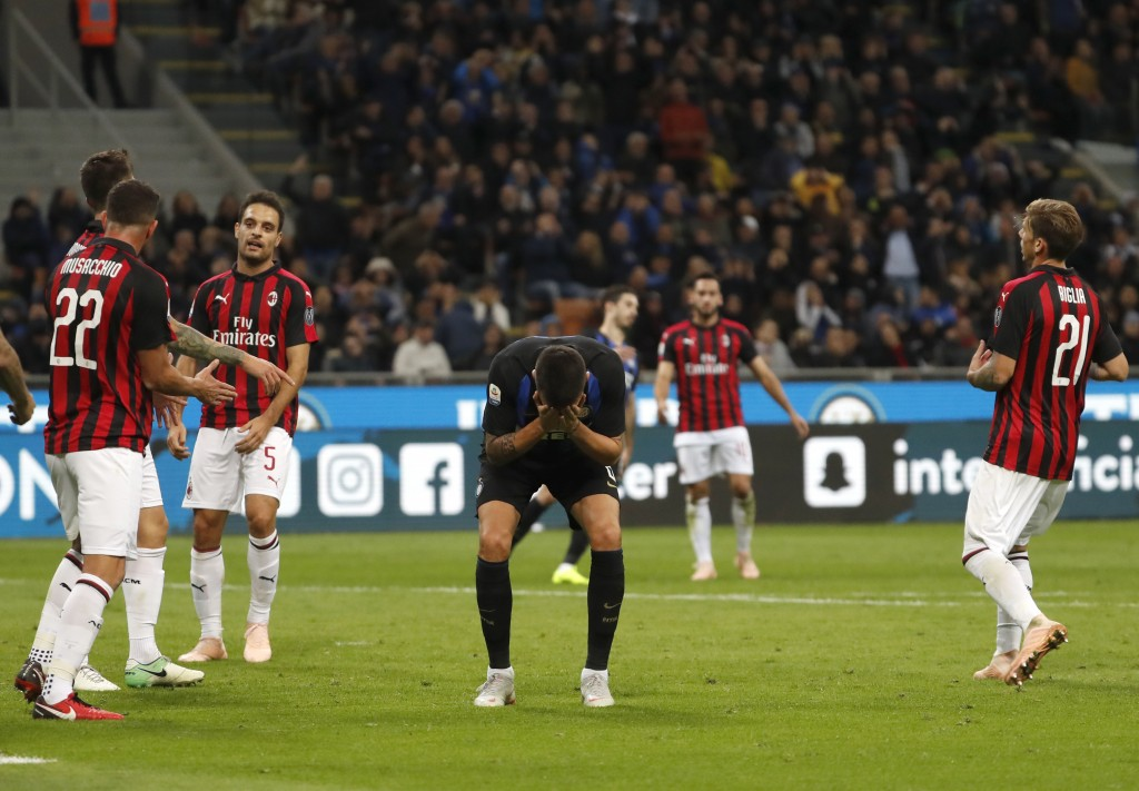 Inter Milan's Matias Vecino, center, reacts after missing a scoring chance during the Serie A soccer match between Inter Milan and AC Milan at the San