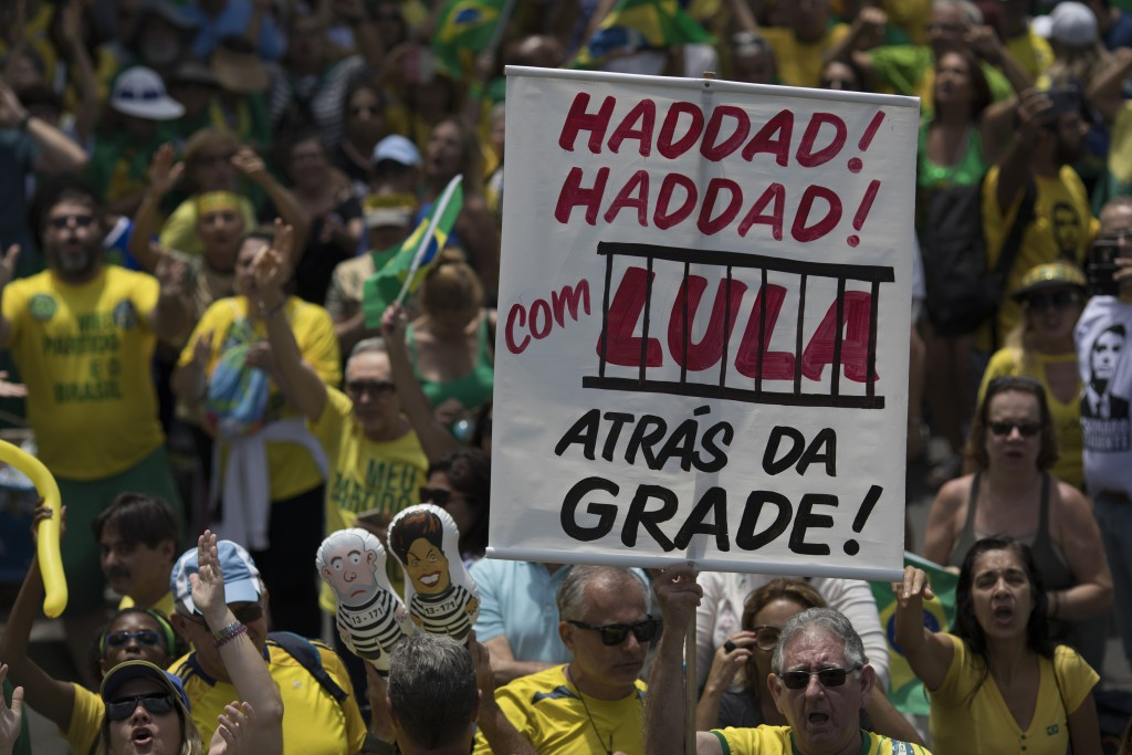 """A man holds a sign that reads in Portuguese """"Haddad with Lula behind the bars,"""" referring to former President Luiz Inacio Lula da Silva, who is in jai"""