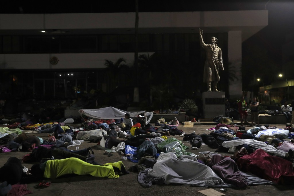 Honduran migrants hoping to reach the U.S. sleep in the southern Mexico city of Tapachula, Monday, Oct. 22, 2018, in a public plaza featuring a statue...