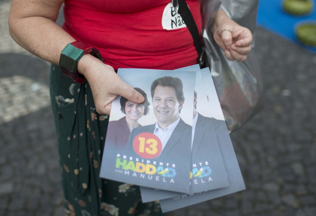In this Oct. 17, 2018 photo, a campaigner holds a stack of flyers for Workers' Party candidate Fernando Haddad, and wears #NotHim stickers against far