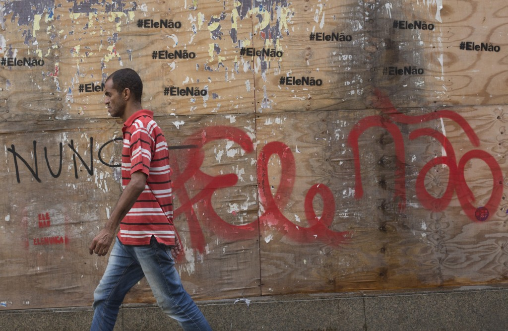 """In this Oct. 17, 2018 photo, a man walks past graffiti that reads in Portuguese: """"Not him"""" in Rio de Janeiro, Brazil.  Polls have consistently shown t"""