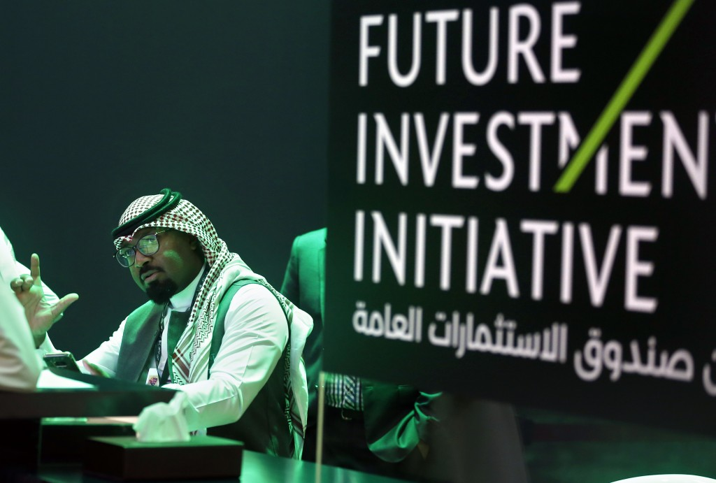 A Saudi employee prints badges of participants of the Future Investment Initiative conference, which kicks off Tuesday, in Riyadh, Saudi Arabia, Monda