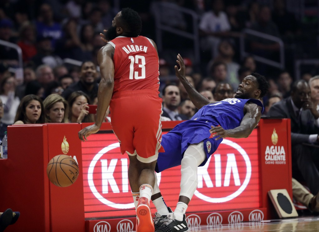 Houston Rockets' James Harden, left, collides with Los Angeles Clippers' Patrick Beverley during the first half of an NBA basketball game Sunday, Oct....