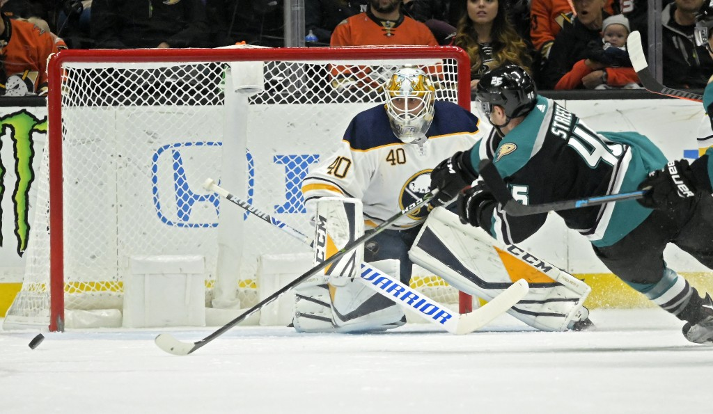 Anaheim Ducks center Ben Street, right, tries to get a shot past Buffalo Sabres goaltender Carter Hutton during the first period of an NHL hockey game...