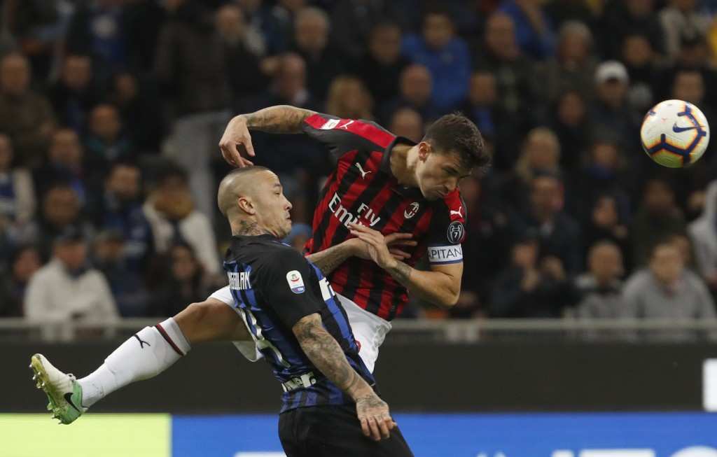 Inter Milan's Radja Nainggolan, left and AC Milan's Alessio Romagnoli compete for the ball during the Serie A soccer match between Inter Milan and AC