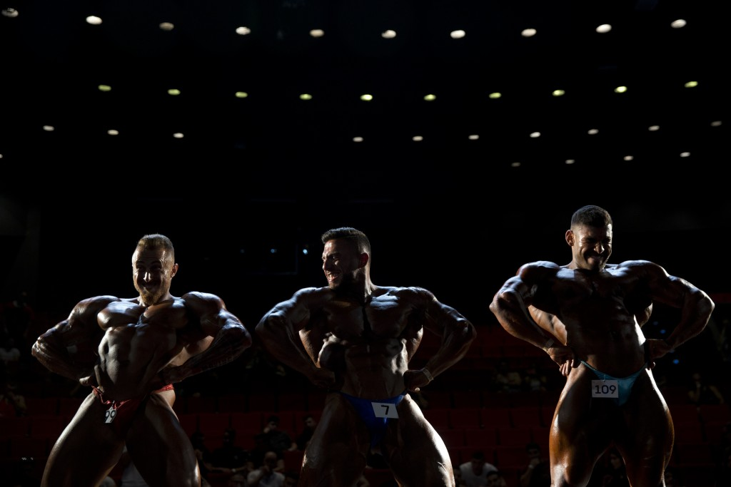 In this Thursday, Oct. 18, 2018 photo, contestants participate in the final round during the National Amateur Body Builders' Association competition i