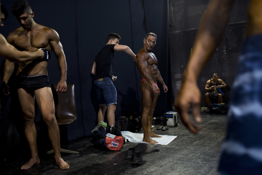 In this Thursday, Oct. 18, 2018 photo, contestants have their body painted backstage  during the National Amateur Body Builders' Association competiti...