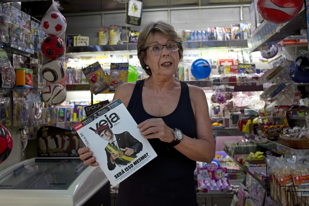 In this Oct. 6, 2018 photo, newsstand owner Rosangela Mesquita poses for a photo holding a Veja magazine depicting Brazil's presidential candidate Jai