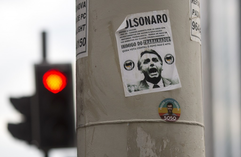 """In this Oct. 17, 2018 photo, a sticker calling presidential candidate Jair Bolsonaro as an """"Enemy of the worker"""" covers a street column in Rio de Jane"""