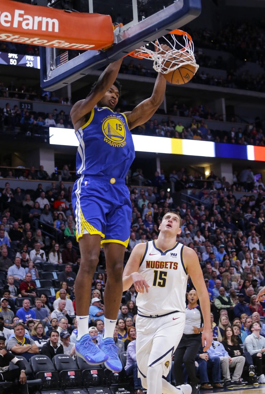 Golden State Warriors center Damian Jones (15) dunks against Denver Nuggets center Nikola Jokic (15) during the first quarter of an NBA basketball gam...