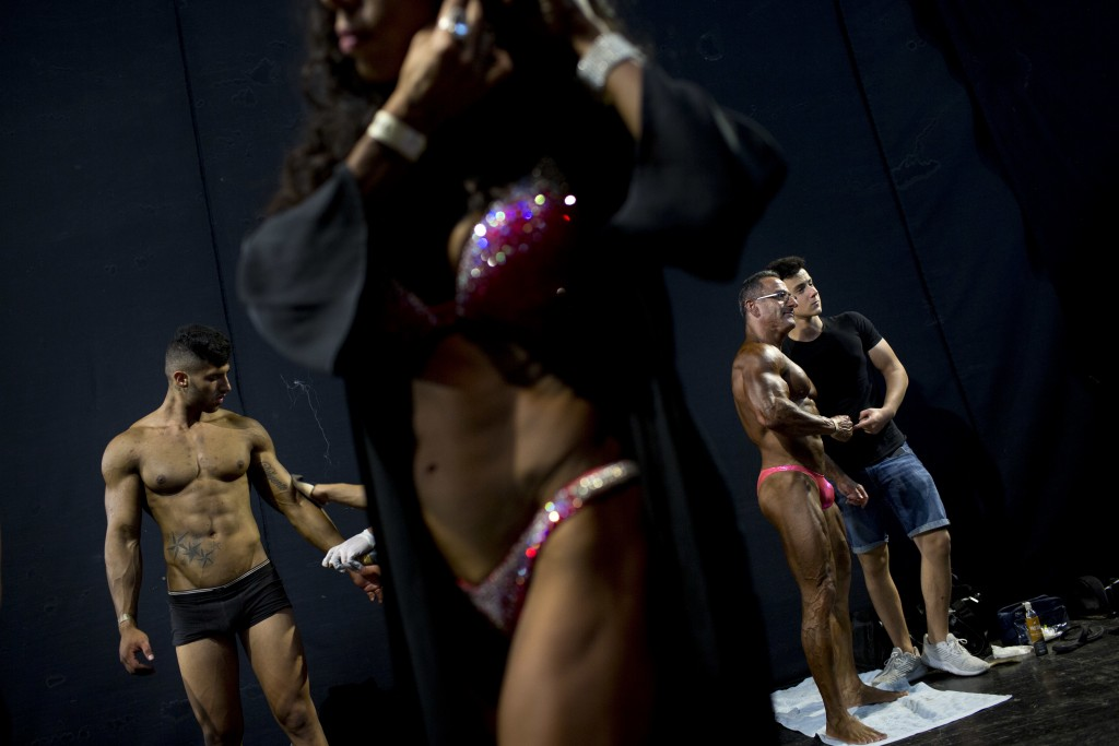 In this Thursday, Oct. 18, 2018 photo, contestants get ready backstage during the National Amateur Body Builders' Association competition in Tel Aviv,