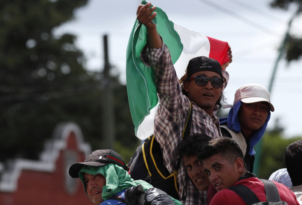 Central American migrants making their way to the U.S. in a large caravan wave a Mexican flag as they arrive to Tapachula, Mexico, after a truck drive...