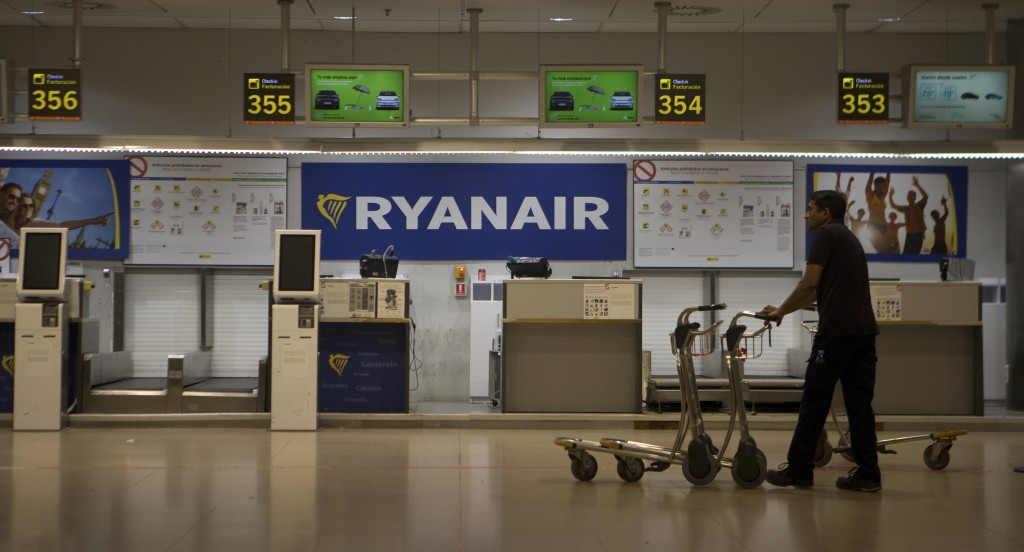 FILE - In this Friday, Aug. 10, 2018 file photo, a worker collects baggage trolleys at the Barajas airport in Madrid, Spain, as Ryanair pilots in seve