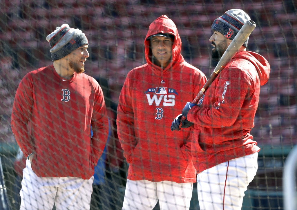 Boston Red Sox manager Alex Cora, middle, chats with catchers, Christian Vazquez, left, and Sandy Leon, right, during a baseball work out at Fenway Pa...