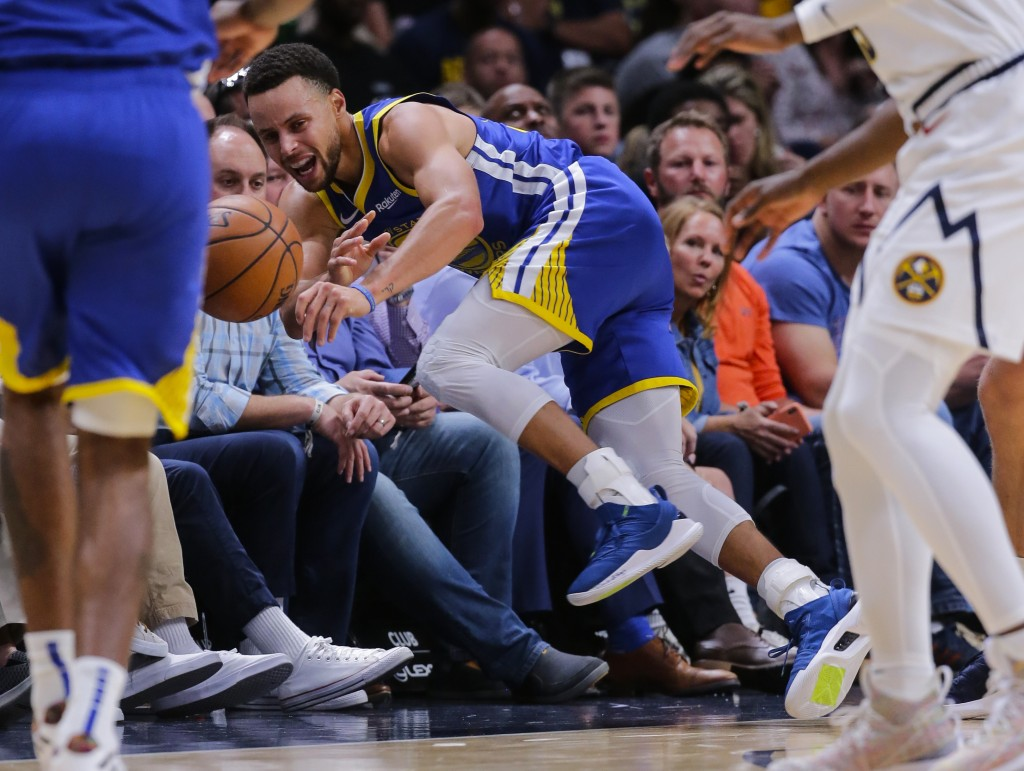Golden State Warriors guard Stephen Curry dives out of bounds during the third quarter of an NBA basketball game against the Denver Nuggets, Sunday, O...