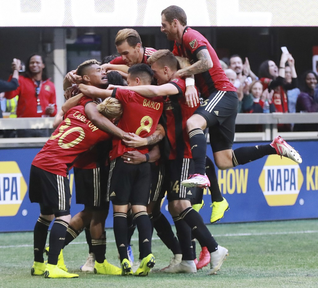 Atlanta United players mob Franco Escobar after his goal for a 1-0 lead over the Chicago Fire during the first half in a MLS soccer match on Sunday, O...