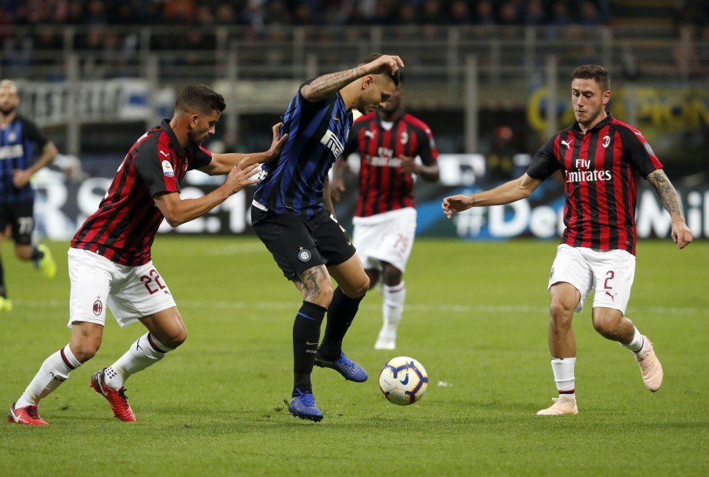 From left, AC Milan's Mateo Musacchio, Inter Milan's Mauro Icardi and AC Milan's Davide Calabria compete for the ball during the Serie A soccer match ...