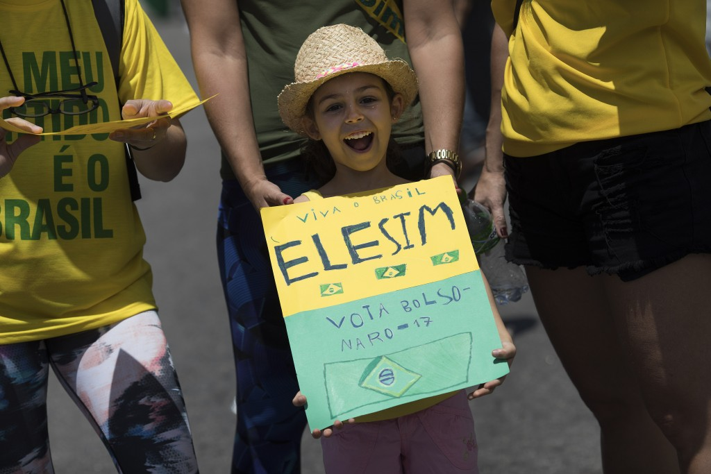 "A girl holds a sign that reads in Portuguese ""Long live Brazil. Him, yes. Vote Bolsonaro"" during a campaign rally for presidential candidate Jair Bols..."