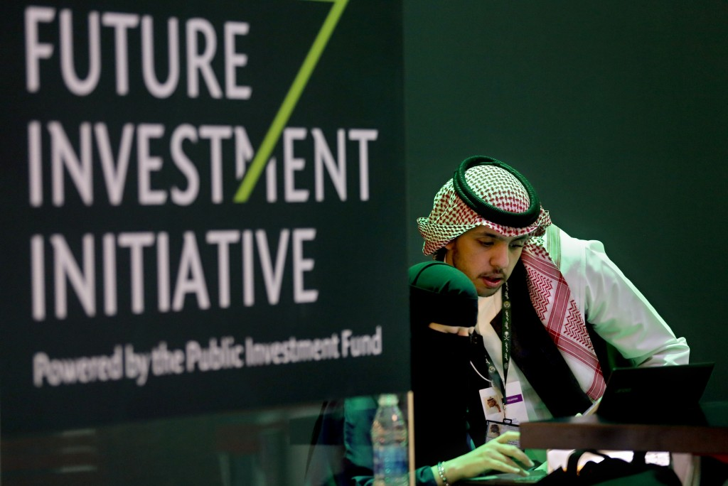 Saudi employees print badges of participants of the Future Investment Initiative conference, which kicks off Tuesday, in Riyadh, Saudi Arabia, Monday,
