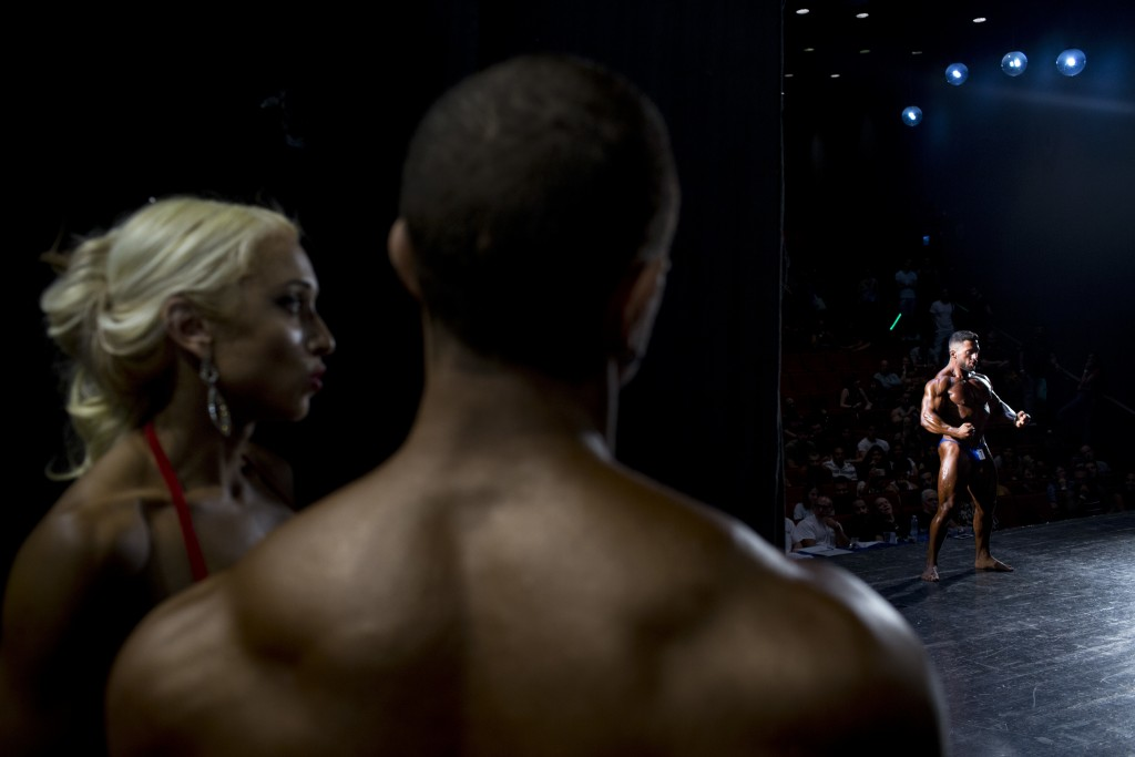 In this Thursday, Oct. 18, 2018 photo, a contestant flexes for the judges during the National Amateur Body Builders' Association competition in Tel Av