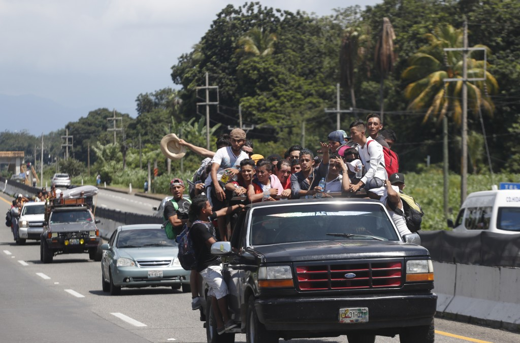 Central American migrants making their way to the U.S. in a large caravan fill the truck of a driver who offered them the free ride, as they arrive to