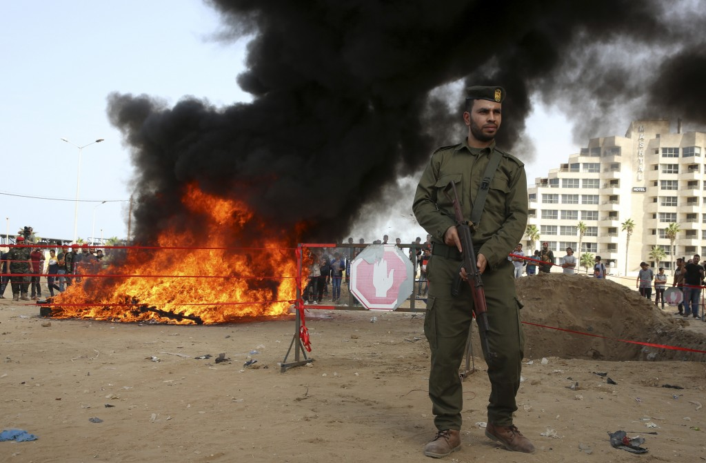 Hamas security forces stand guard while they burn some 1,383 bars of hashish and 1,242,000 pills of Tramadol, that have been seized since the beginnin...