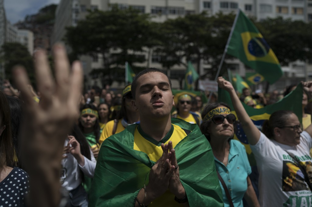 A man listens to Brazil's anthem during a campaign rally for presidential candidate Jair Bolsonaro, of the far-right Social Liberal Party, at Copacaba